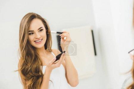 mirror reflection of beautiful young woman applying makeup