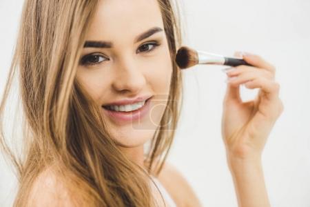portrait of smiling beautiful woman applying makeup