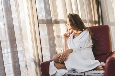 pretty smiling woman in bathrobe resting on armchair at home