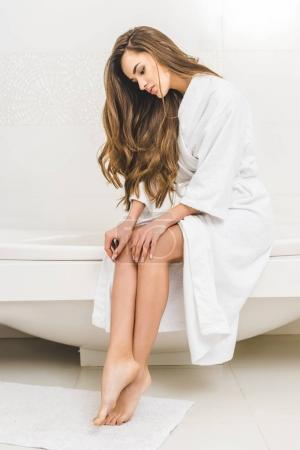 young woman in bathrobe sitting on bath tube at home