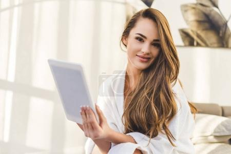 Photo for Portrait of young woman in bathrobe with tablet sitting on bed at home - Royalty Free Image
