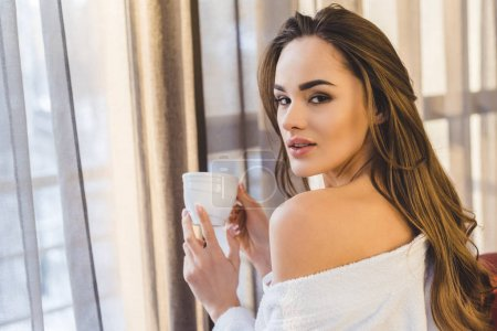 side view of beautiful young woman in bathrobe with cup of coffee at home