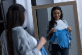 african american pregnant woman holding baby bodysuit and looking at reflection in mirror