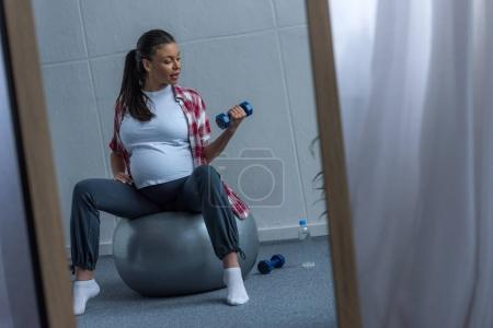 mirror with reflection of african american pregnant woman sitting on fit ball and training with dumbbells