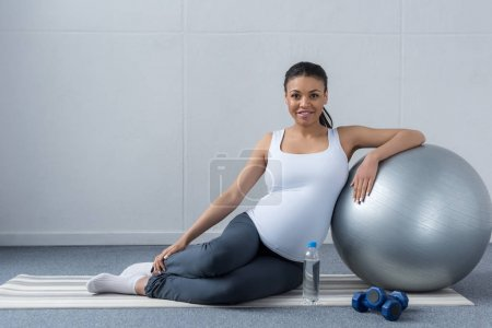 smiling african american pregnant woman sitting with fit ball with water and dumbbells