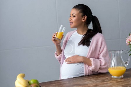 african american pregnant woman with glass of orange juice at kitchen