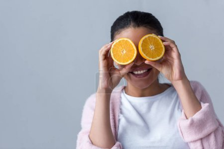 cheerful african american girl with halves of orange, isolated on grey