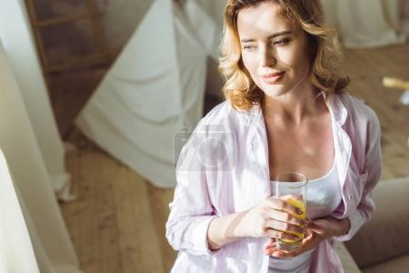 attractive woman in pajamas with orange juice in the morning