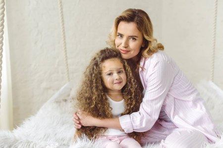 Foto de Feliz madre abrazando a su adorable hija rizada - Imagen libre de derechos