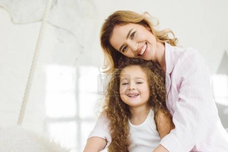 Photo pour Joyeuse mère et adorable fille regardant la caméra - image libre de droit