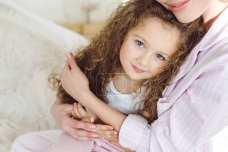 mother hugging her adorable smiling daughter