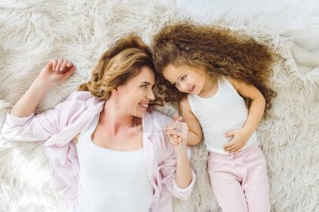 top view of smiling mom and curly daughter relaxing and looking at each other