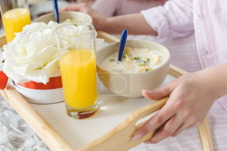 cropped view of woman holding tray with yogurt and orange juice for breakfast