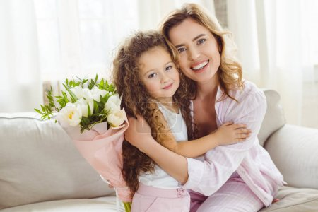 Photo for Hugging daughter and mother with bouquet for happy mothers day - Royalty Free Image