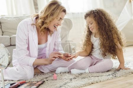 Photo for Mother and daughter in pajamas making manicure at home - Royalty Free Image