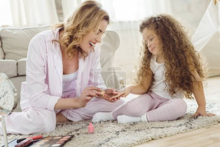 mother and daughter in pajamas making manicure at home