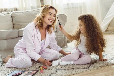 happy mother and daughter in pajamas applying makeup at home