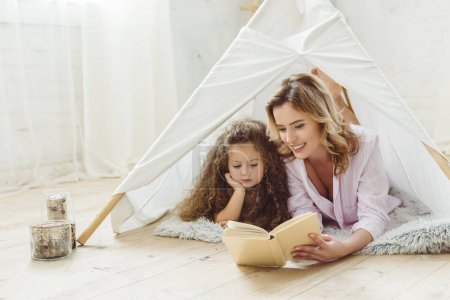 Photo for Happy mother and daughter reading book together in kid wigwam - Royalty Free Image