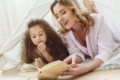 beautiful mother and daughter reading book in kid wigwam