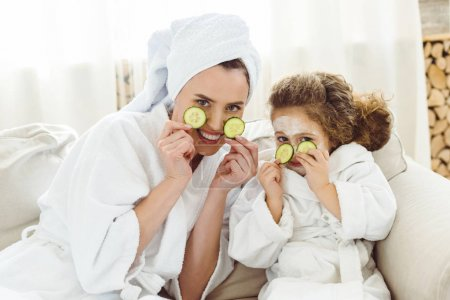 Photo for Happy mother and daughter with cucumber slices doing cosmetic procedures - Royalty Free Image