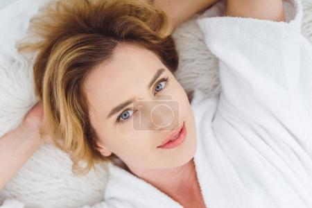 top view of beautiful woman lying in bed and looking at camera