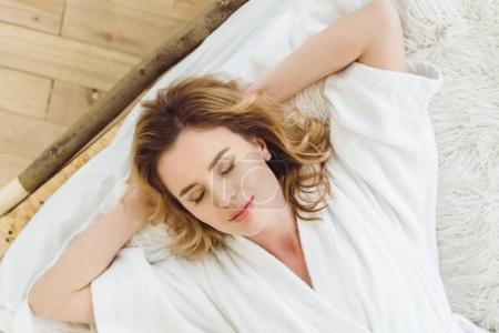 top view of beautiful woman relaxing with closed eyes in bed at home