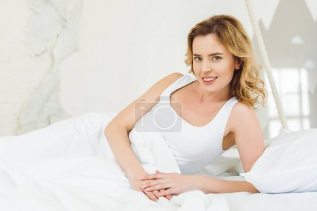 attractive woman lying in bed at home