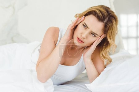 blonde woman having headache and lying in bed at home