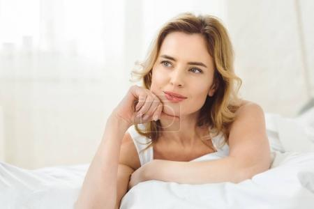 thoughtful attractive woman lying in bed at home