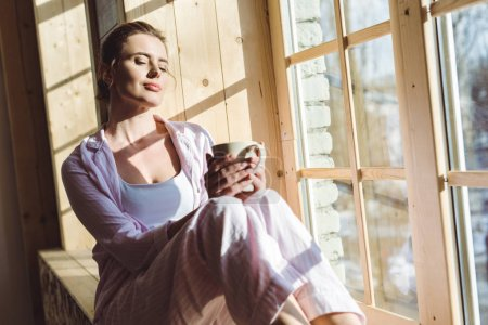 Photo for Attractive dreamy woman with closed eyes holding cup of coffee and sitting on windowsill - Royalty Free Image