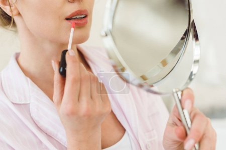 cropped view of woman looking at mirror and applying lip gloss