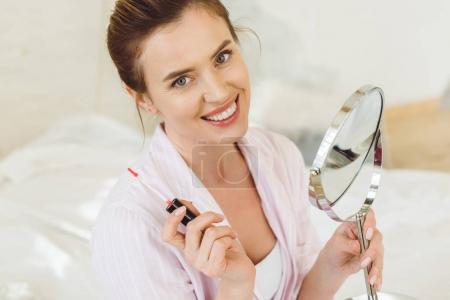 beautiful smiling woman holding lip gloss and mirror