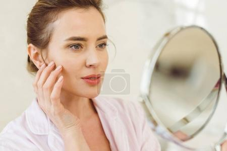 beautiful woman looking at her skin in mirror
