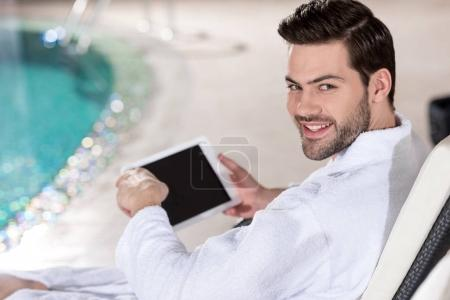 handsome young man in bathrobe holding digital tablet and smiling at camera in spa center