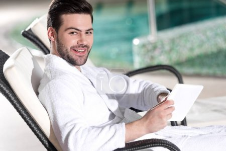 handsome man in bathrobe holding digital tablet and smiling at camera in spa center