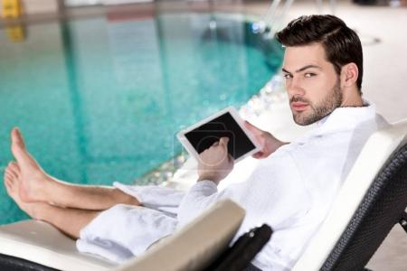 handsome man in bathrobe using digital tablet and looking at camera in spa center