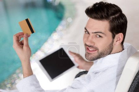 smiling young man in bathrobe holding credit card and digital tablet in spa center