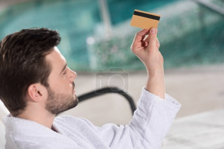 handsome young man in bathrobe holding credit card in spa center