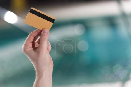 cropped shot of man holding credit card in spa center