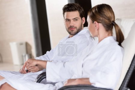 young couple in bathrobes holding hands and looking at each other while resting together in spa center