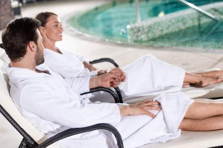 side view of happy young couple in bathrobes sitting near pool in spa center