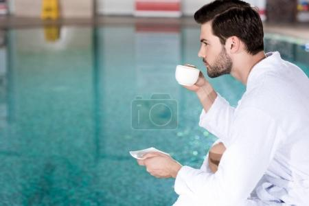 side view of man in bathrobe drinking coffee while sitting near pool in spa center