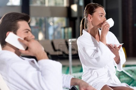 young couple in bathrobes talking by smartphone and drinking coffee near pool in spa center