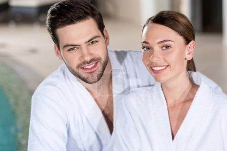 Photo pour Beau jeune couple en peignoirs, souriant à la caméra dans le centre de bien-être - image libre de droit