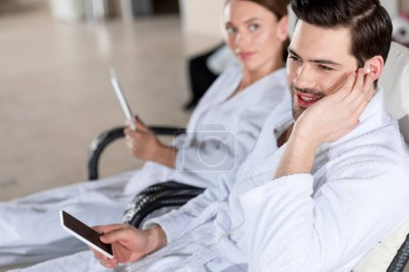 young couple in bathrobes using digital devices while resting together in spa center