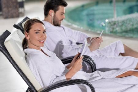 young couple in bathrobes using digital devices while resting near pool in spa center