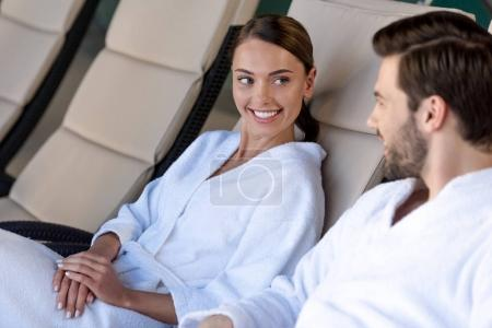 happy young couple in bathrobes smiling each other while resting together in spa center
