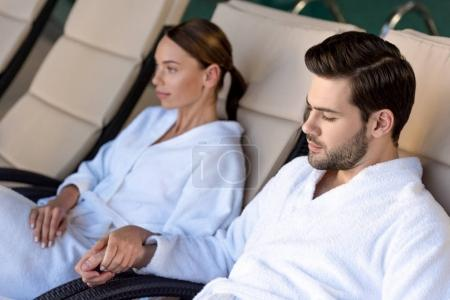 young couple in bathrobes holding hands while resting together in spa center