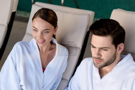 happy young couple in bathrobes smiling and looking away in spa center