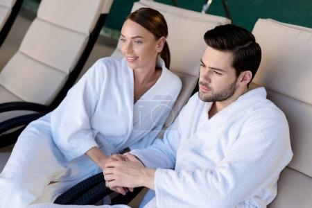 happy young couple in bathrobes holding hands and looking away in spa center